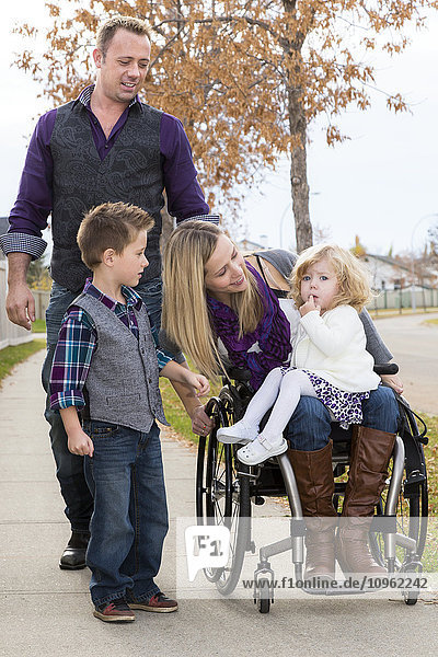 'Disabled young mother spending quality time with her family outdoors; Spruce Grove,  Alberta,  Canada'