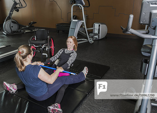 'Physiotherapist assisting young woman with spinal cord injury in performing back extension exercises; Edmonton  Alberta  Canada'