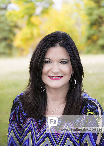 'Portrait of a beautiful mature woman outdoors in a city park in autumn; St. Albert  Alberta  Canada'