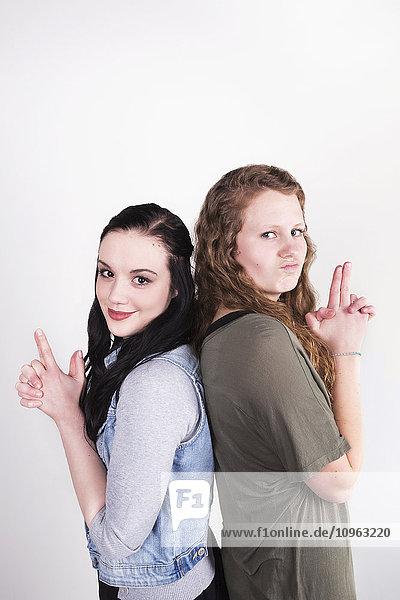 'Two young women pretending to have smoking guns; Alberta  Canada'
