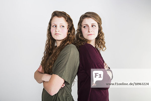'Studio shot of two girlfriends fighting  on a white background; Alberta  Canada'