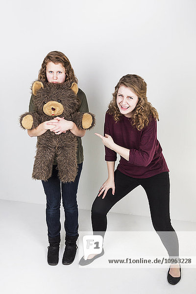 'Studio shot of one friend making fun of another friend holding her teddy bear; Alberta  Canada'