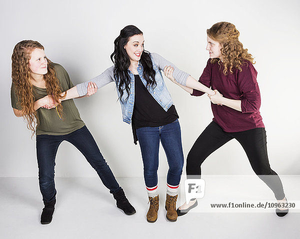 'Studio shot of two friends fighting over a common friend; Alberta  Canada'