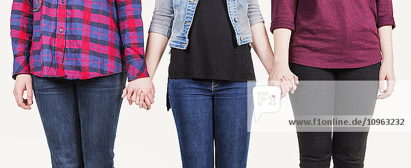 'Three young women holding hands committed to teamwork; Alberta  Canada'