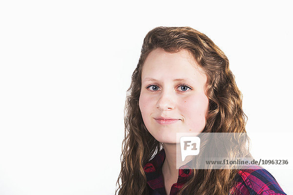 'Portrait of a young woman with long  curly hair on a white background; Alberta  Canada'