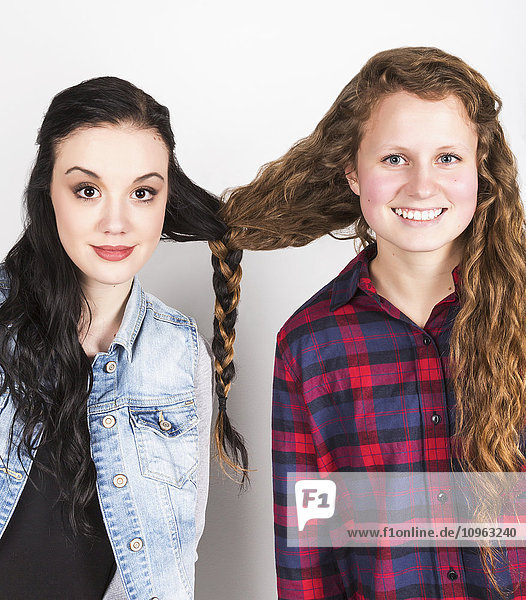 'Studio portrait of two young women with their hair braided together; Alberta  Canada'
