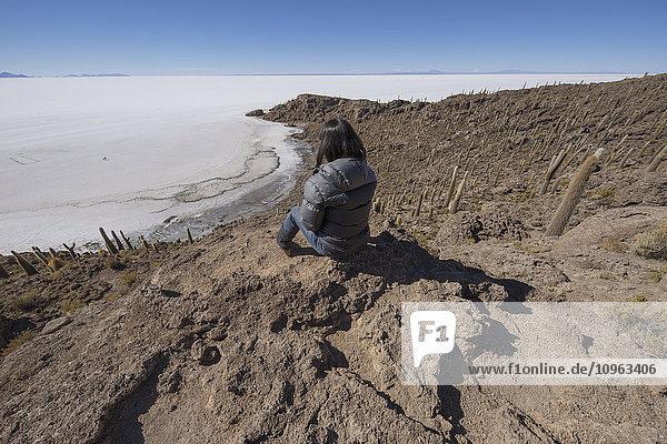 'Woman sitting on an island of rock and cactus called Incahuasi; Uyuni  Bolivia'
