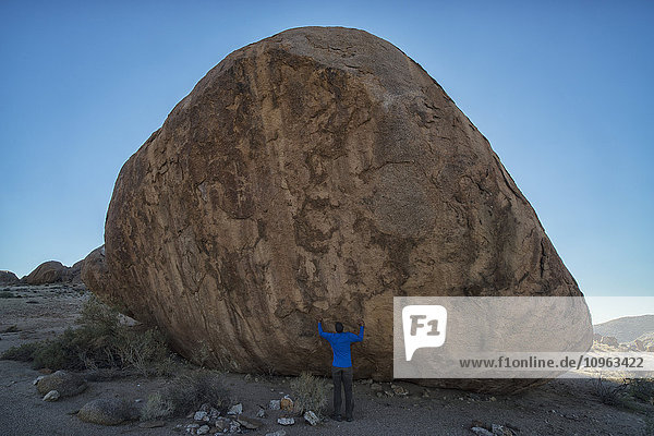 'Person standing under a large boulder in Richtersveld National Park; South Africa'