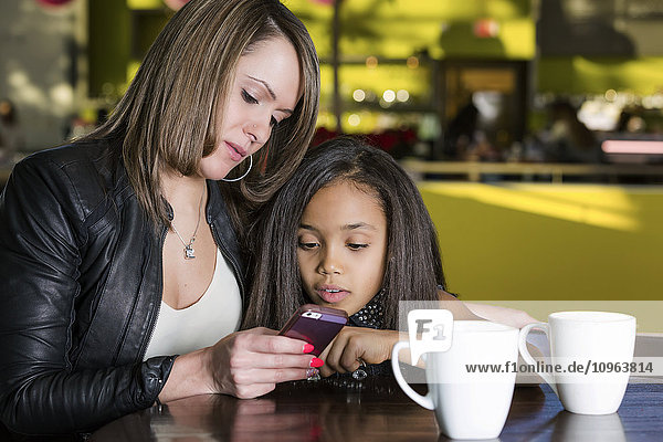 'Young mother and her daughter in a cafe looking at a smart phone while taking a break from shopping; St. Albert  Alberta  Canada'