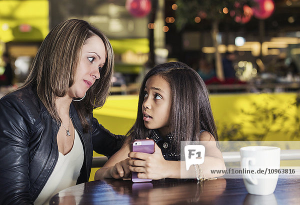 'Young mother and her daughter in a cafe looking at a smart phone while taking a break from shopping and being concerned about content being viewed; St. Albert  Alberta  Canada'