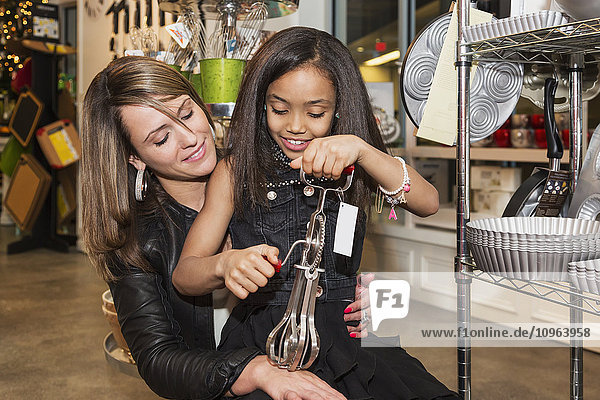 'Young mother and her daughter shopping at a kitchen store looking at an egg beater; St. Albert  Alberta  Canada'