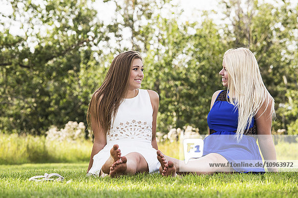 'Two girlfriends spending time together in a park wearing dresses; Edmonton  Alberta  Canada'