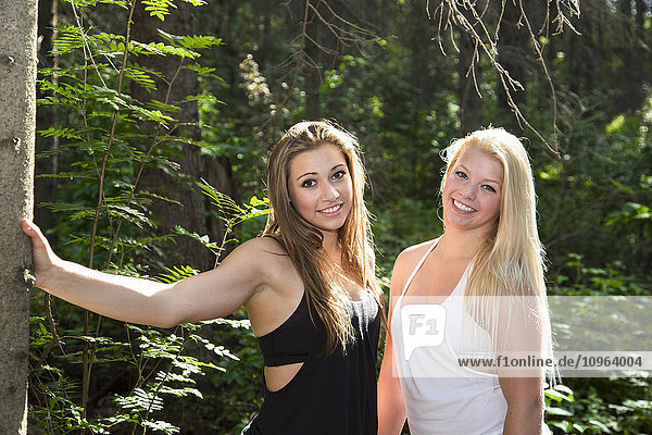 'Two girlfriends posing together in the woods in the sunshine; Edmonton  Alberta  Canada'