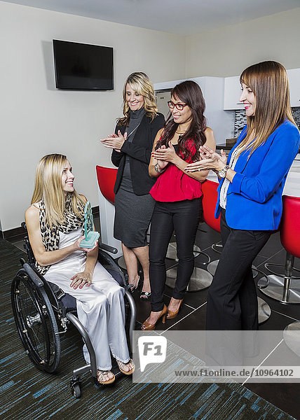'Co-workers applauding the achievements of disabled peer; St. Albert  Alberta  Canada'
