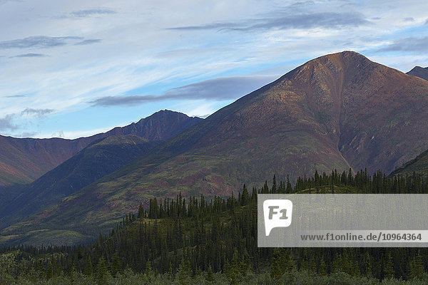'Late afternoon light shining on the mountains along the Wind River in the Peel Watershed; Yukon  Canada'
