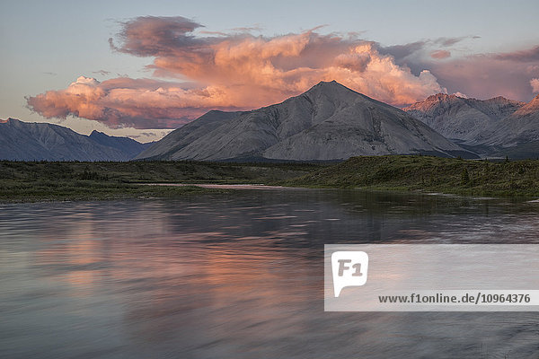 'The midnight sun shines on the mountains and clouds lining the Wind River in the Peel watershed; Yukon  Canada'