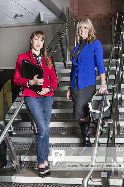 'Portrait of two professional business women on a stairway in an office; St. Albert  Alberta  Canada'