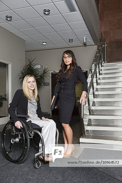 'Portrait of two professional business women in the lobby of an office  one of which is a paraplegic in a wheelchair; St. Albert  Alberta  Canada'