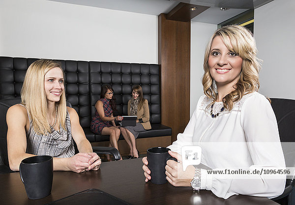 'Four professional business women meeting in a boardroom; St. Albert  Alberta  Canada'