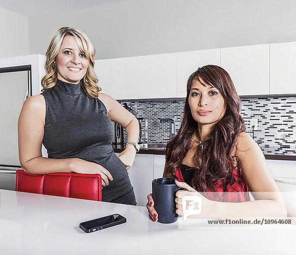 'Two professional business women taking a break in an office kitchen area; St. Albert  Alberta  Canada'