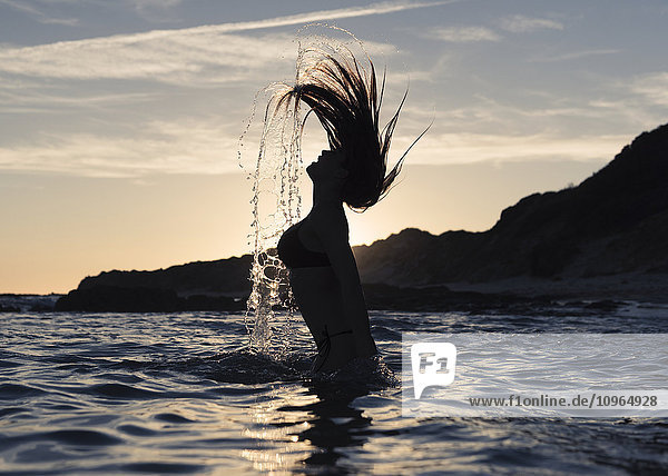 'Silhouette of a woman in waist-deep water flipping her wet long hair up in the air; Tarifa  Cadiz  Andalusia  Spain'