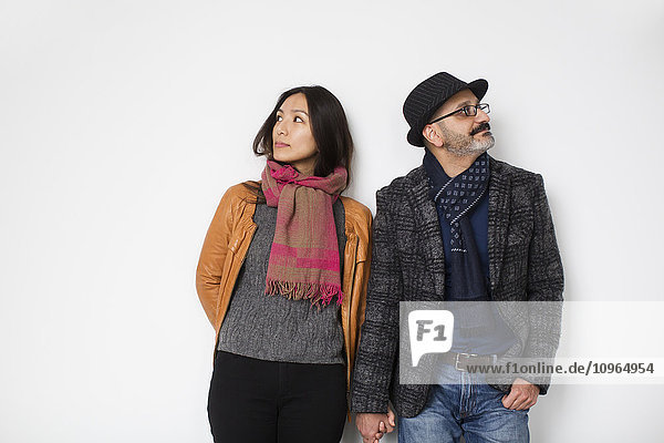 'Persian man and Tibetan woman holding hands and leaning against a wall facing away from each other; Toronto  Ontario  Canada'