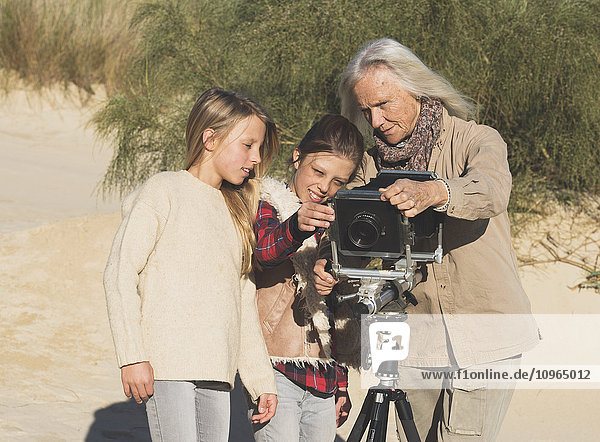 'A female photographer shows two young girls images on a camera with tripod on the beach; Tarifa  Cadiz  Andalusia  Spain'