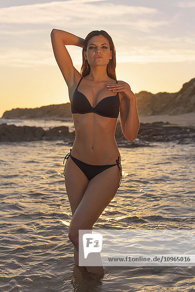 'Woman in black bikini standing in the shallow water at the coast at sunset; Tarifa  Cadiz  Andalusia  Spain'