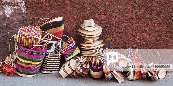 'Woven souvenirs on display on a sidewalk against a wall; San Miguel de Allende  Guanajuato  Mexico'