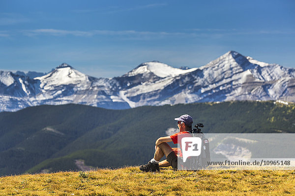 'Male hiker sitting on a grassy mountain top overlooking foothills  snow capped mountain range and blue sky with clouds; Kananaskis Country  Alberta  Canada'