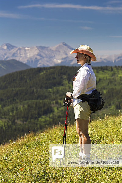 'Female hiker on top of grassy hill overlooking rolling foothills with mountain range in the background with blue sky; Kananaskis Country  Alberta  Canada'