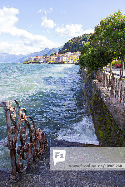 'Wind sends Lake Como water splashing against a waterfront staircase and sidewalk; Bellagio,  Italy'