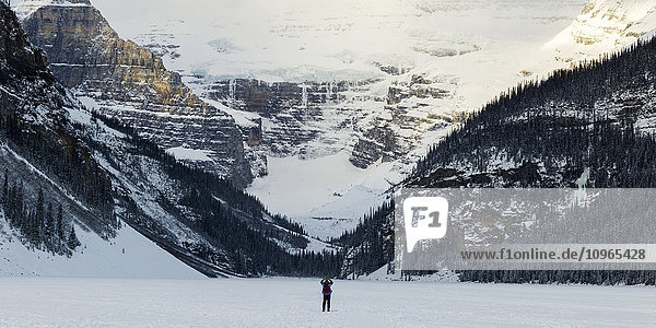 'A person standing on frozen Lake Louise taking a picture of the snow covered mountains; Lake Louise  Alberta  Canada'