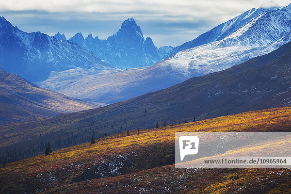 'The north Klondike valley lights up along the Dempster Highway with Tombstone mountain in the distance; Yukon  Canada'