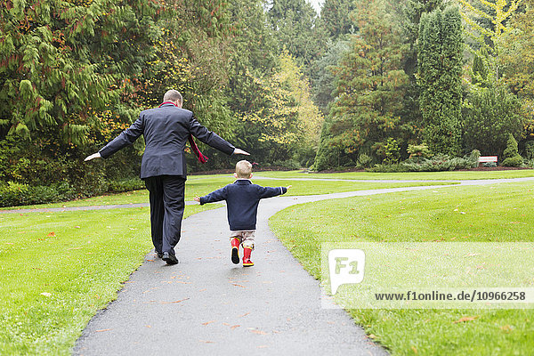 'A father and son walking down a path in Bear Creek Park; Surrey  British Columbia  Canada'