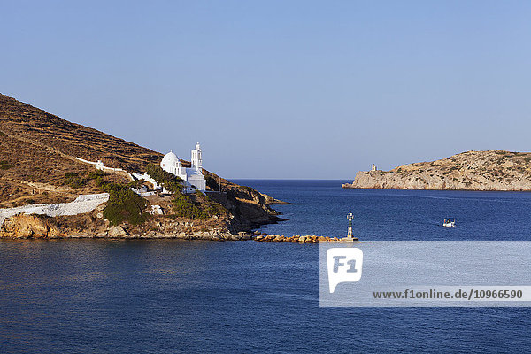 'Port and white church on a cliff at the water's edge; Ios  Greece'