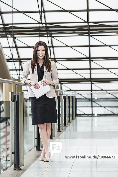'Mature business woman posing in an atrium of an office building and holding a tablet; Edmonton  Alberta  Canada'