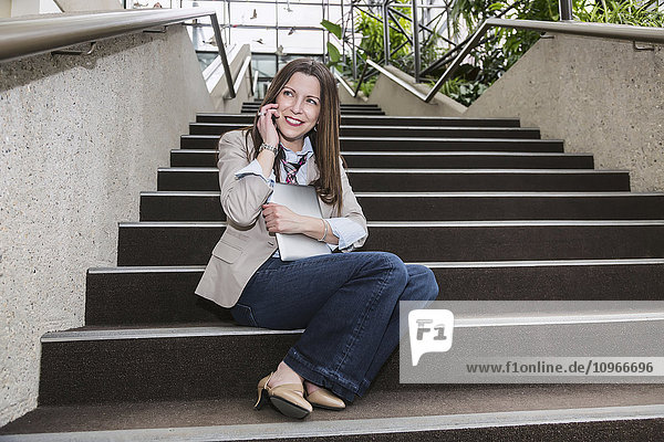 'Mature business woman talking on her cell phone and holding a tablet while sitting on stairway in the atrium of an office building; Edmonton  Alberta  Canada'