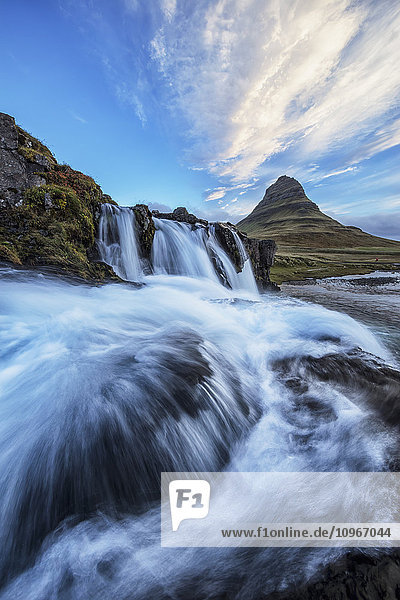 'A waterfall flows in the foreground of Kirkjufell  the most iconic and photographed mountain in Iceland; Iceland'