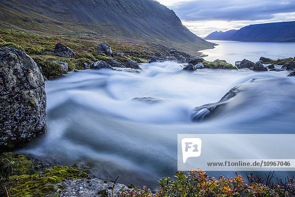 'The water from the large waterfall called Dynjandi flows by in this long exposure on its way to the ocean; Westfjords  Iceland'
