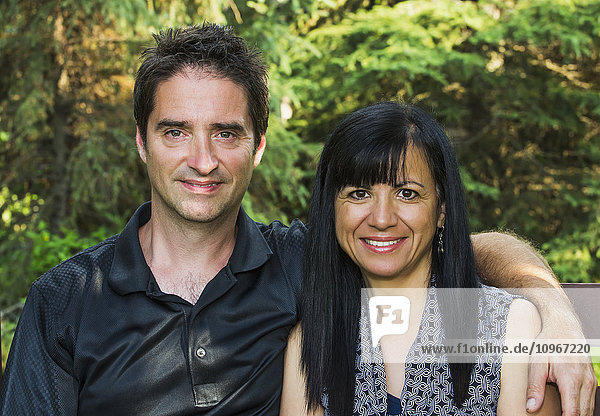 'Portrait of a mature couple outdoors on a bench in autumn; Sherwood Park  Alberta  Canada'
