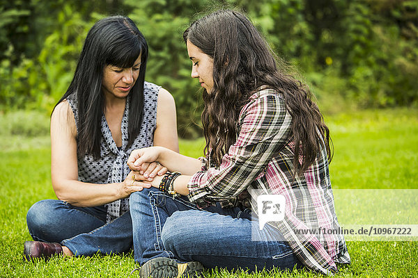 'A mother praying with her daughter outdoors; Sherwood Park  Alberta  Canada'