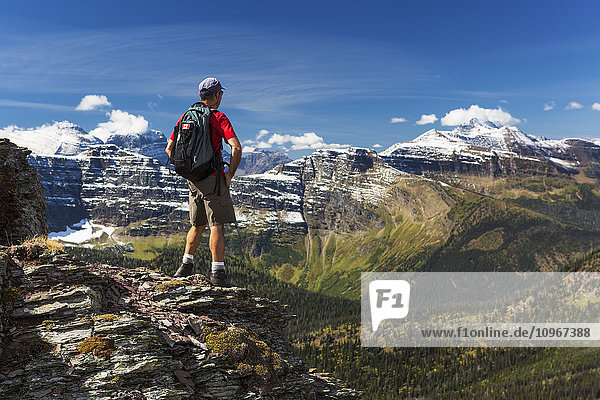 'Male hiker standing on top of mountain ridge overlooking snow peaked mountains and forest valley below with blue sky and clouds; Waterton  Alberta  Canada'