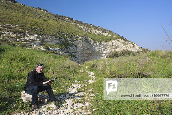 'Man sitting on a rock and reading his Bible in the Valley of Elah; Israel'
