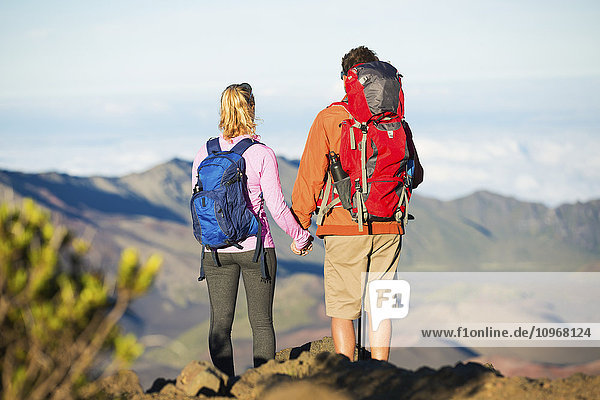 Two hikers relaxing enjoying the amazing view from the mountain top. Looking out over the volcano crater.
