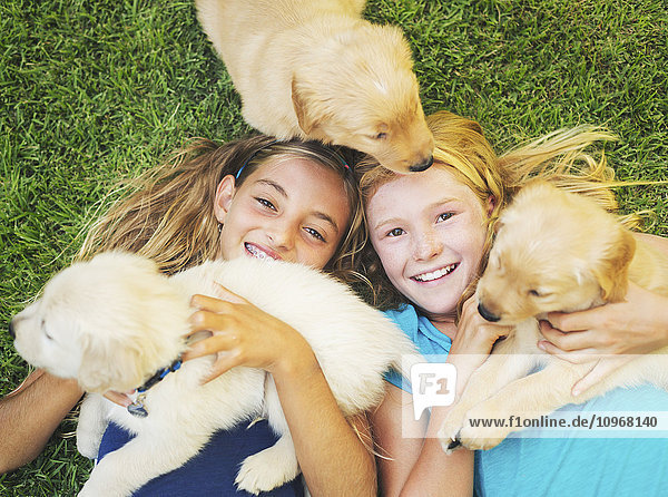 Adorable Cute Young Girls Playing and Hugging Puppies