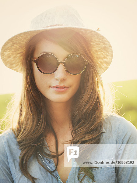 Fashion portrait of beautiful young woman in hat and sunglasses oustide  bright warm sunny color tones