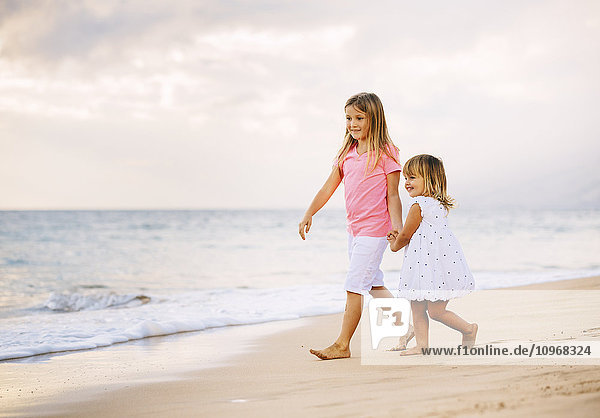 Adorable Young Sisters  Two Little Girls Walking together on the Beach at Sunet  Family Lifestyle.
