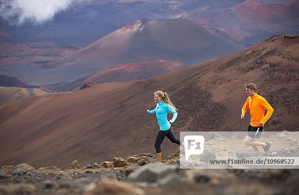 Fitness sport couple jogging outside  training together outdoors. Running on amazing trail at sunset  Dramatic beautiful volcano landscape