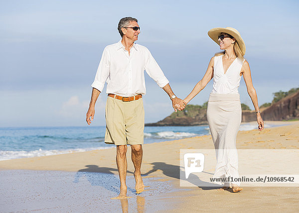 Happy Romantic Middle Aged Couple Enjoying Walk on the Beach  Vacation Retirement Concept